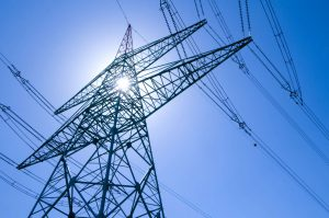 Electricity pylon with blue sky and sun